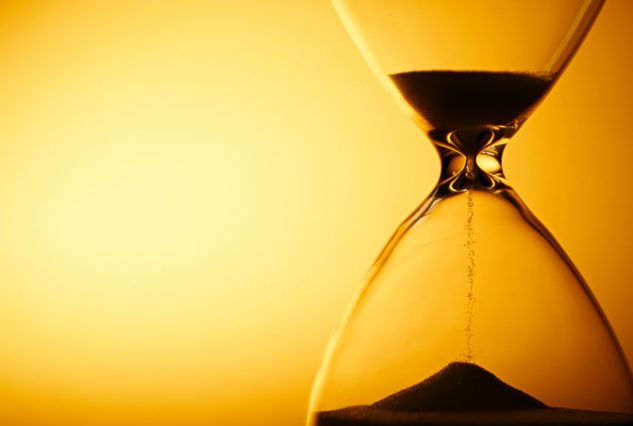 30765483 - sand passing through the glass bulbs of an hourglass measuring the passing time as it counts down to a deadline or closure on a yellow background with copyspace