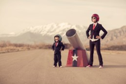 Woman and child in business suits and sunglasses stook either side of a circus cannon