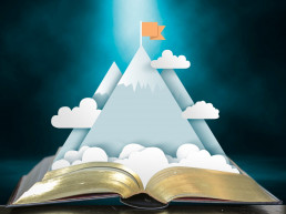 Story book open with illustrated mountains climbing up from the pages