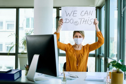 Woman holding a sign in an office saying we can do this