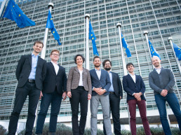 A group of people in front of European flags and an office block